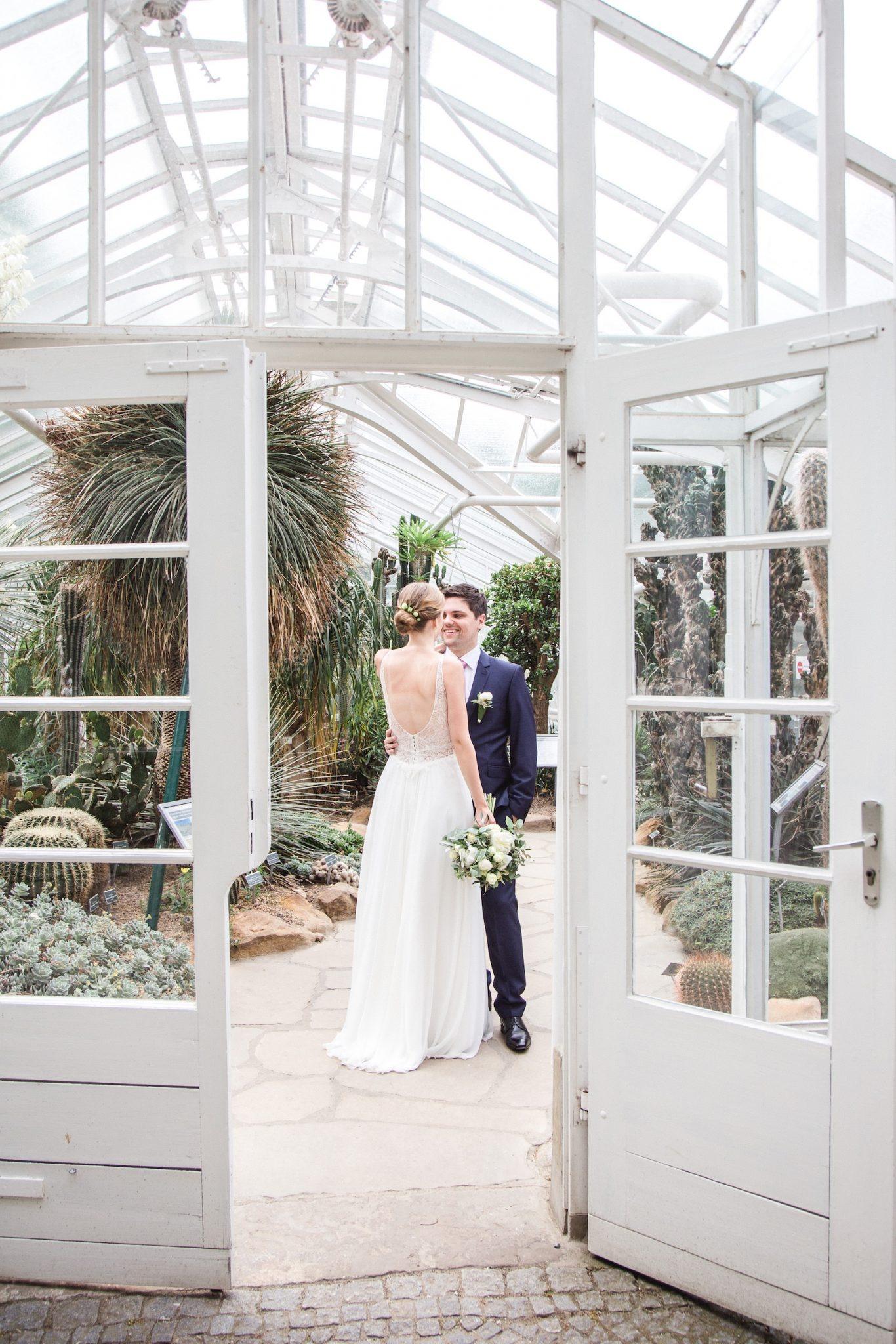 Hochzeit von Du und Ich in Münster: Brautpaar steht im Gewächshaus hinter der Türe