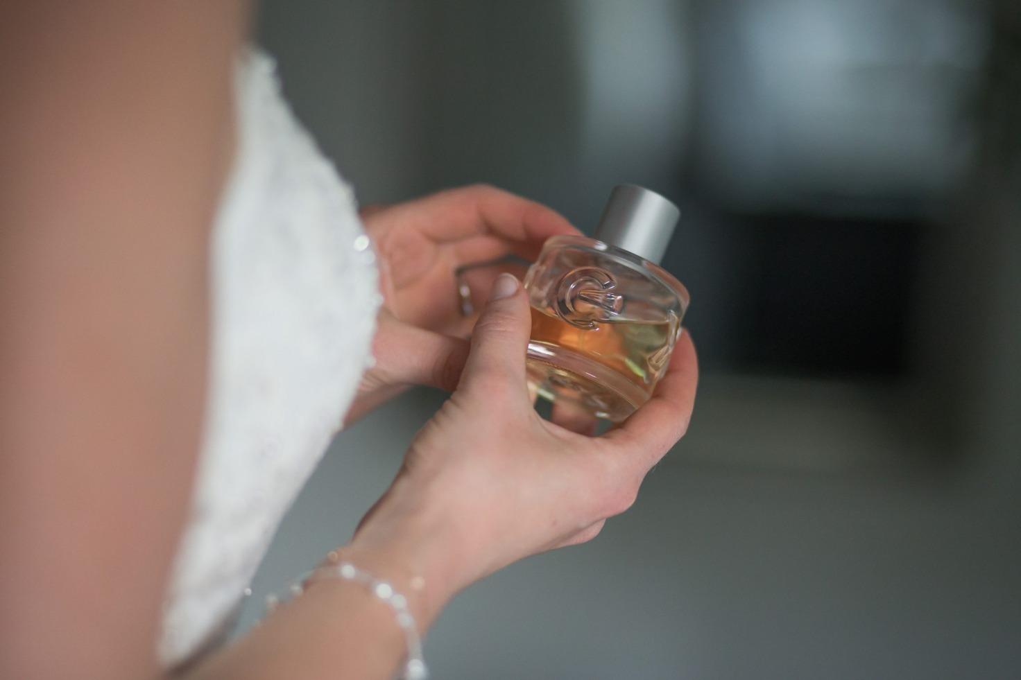 Hochzeit von Tine und Basti in Münster: Braut hält ein Parfüm