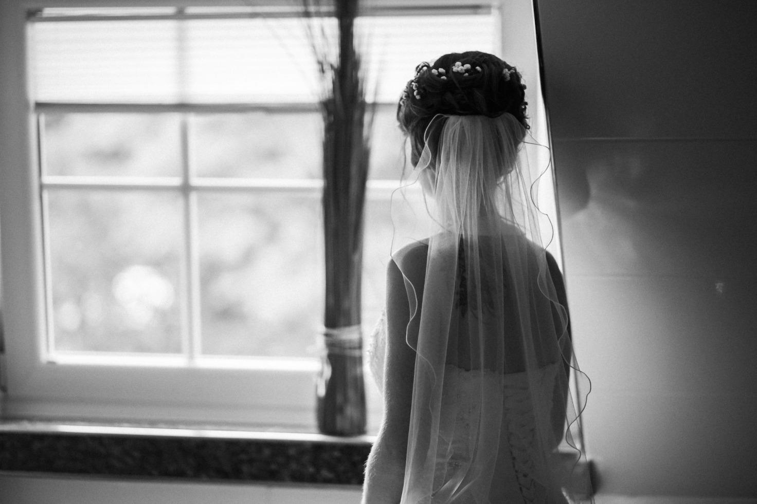 Hochzeit von Tine und Basti in Münster: Braut schaut aus dem Fenster