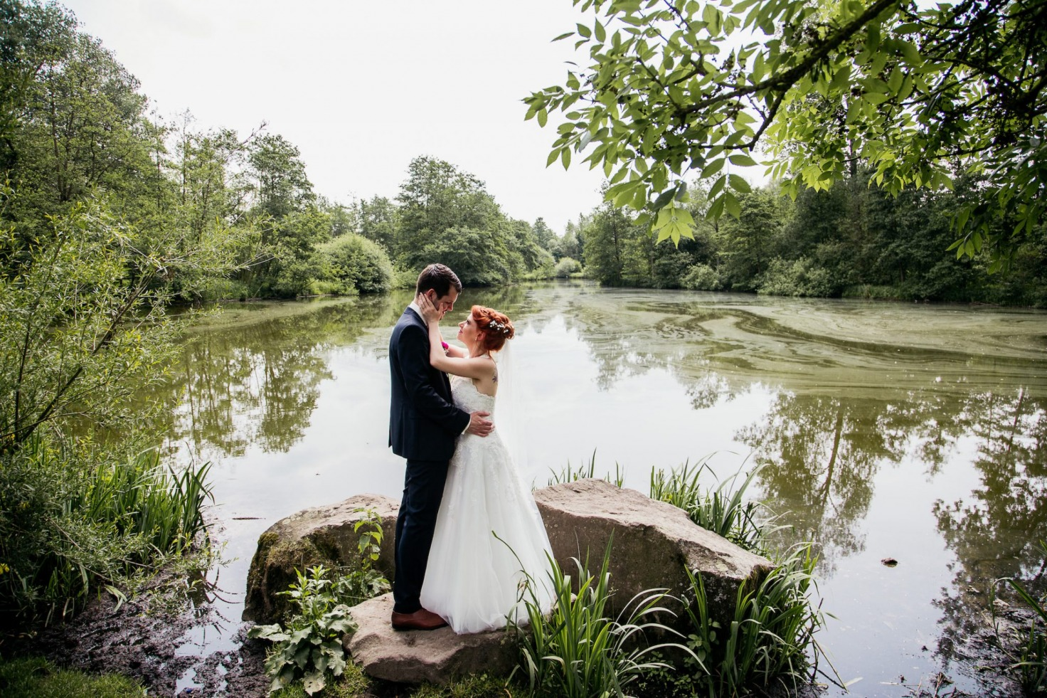 Hochzeit von Tine und Basti in Münster: Brautpaar steht vor einem See