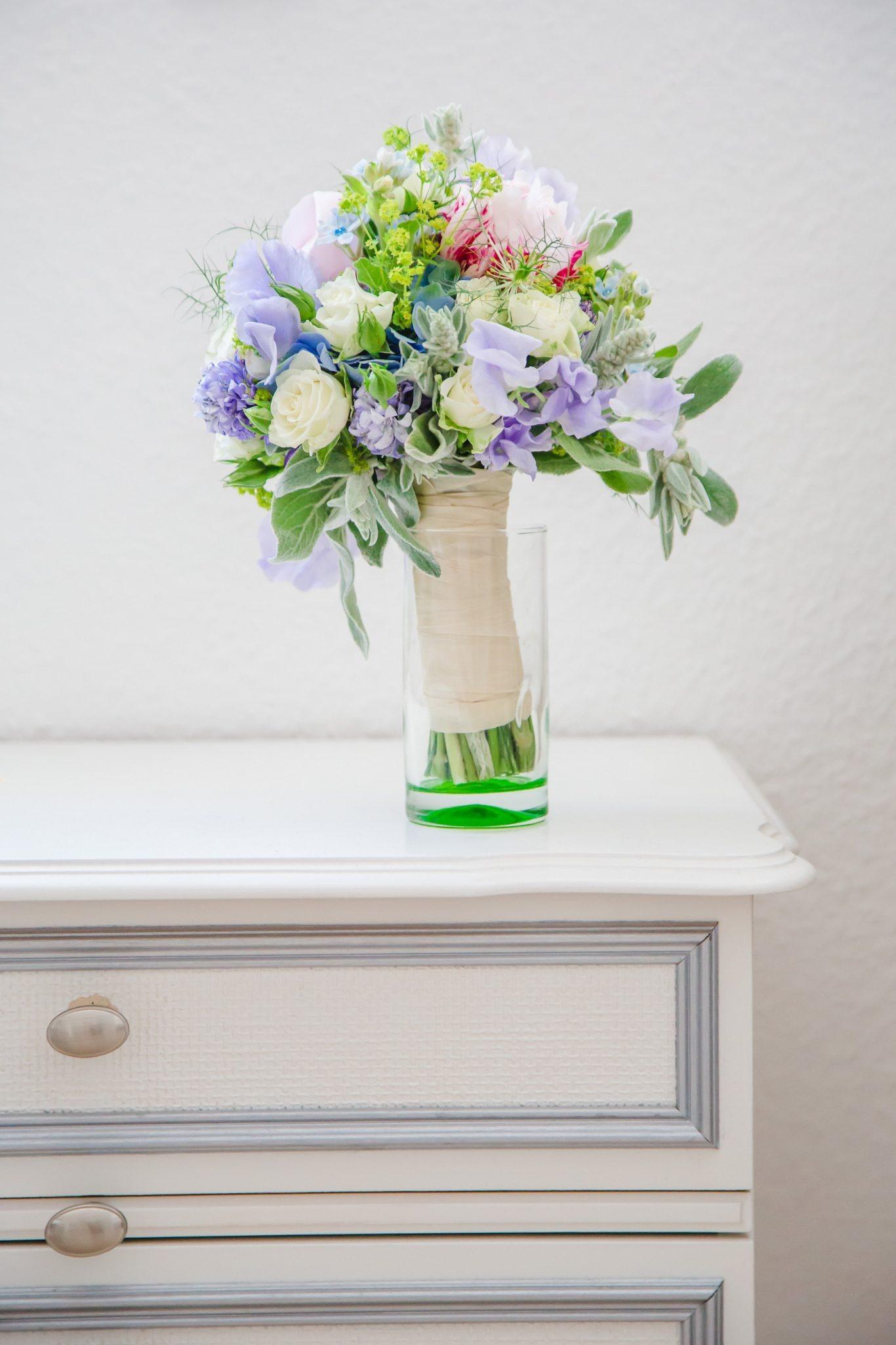 Hochzeit von Tine und Basti in Münster: Brautstrauß auf einer Kommode