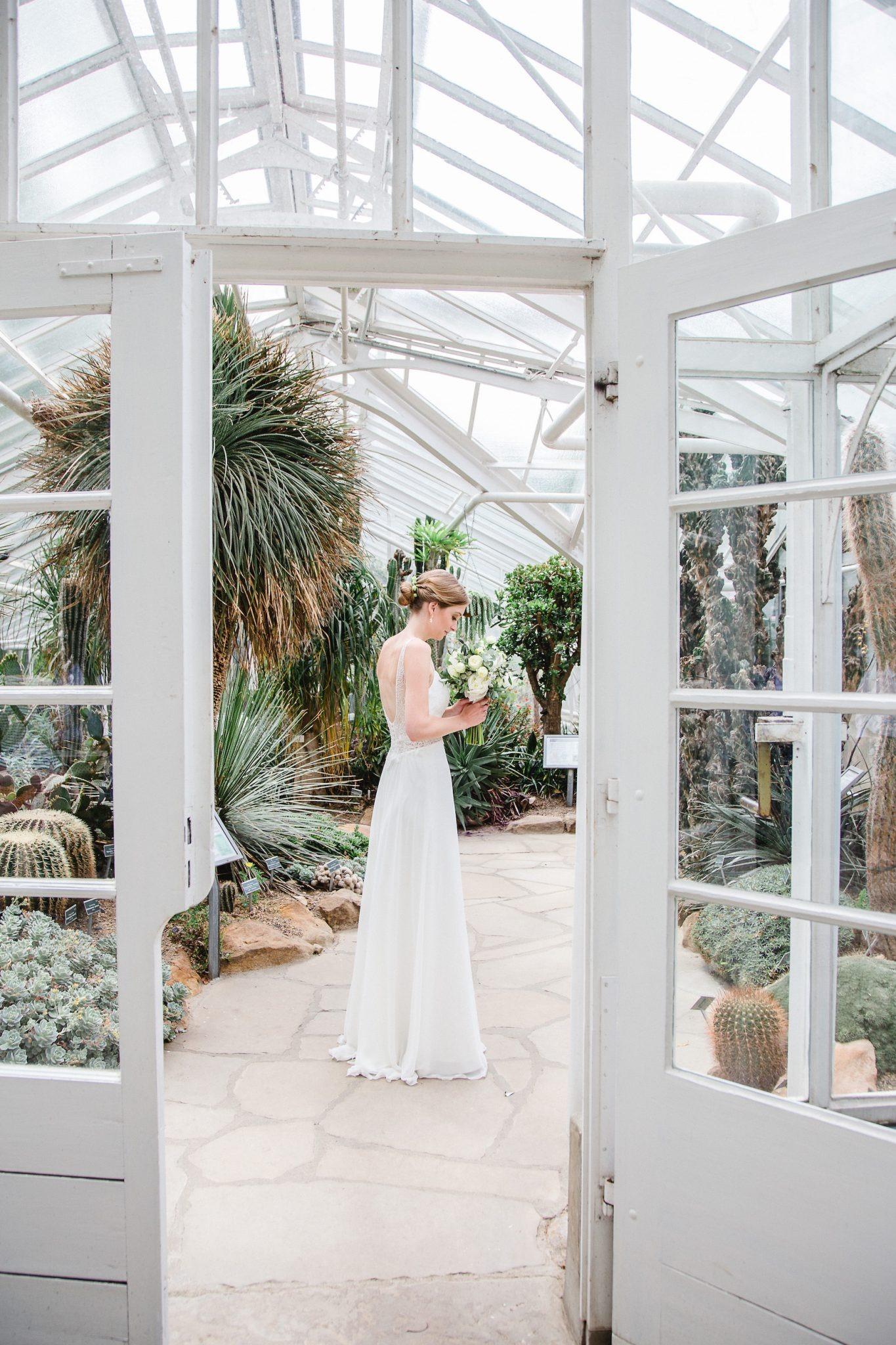 Hochzeit von Du und Ich in Münster: Braut schaut ihren Brautstrauß an
