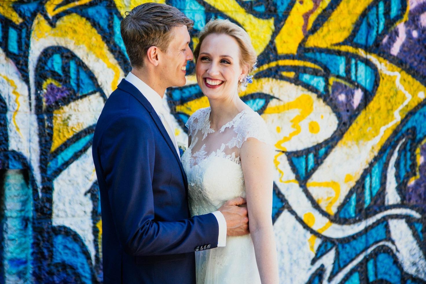 Hochzeit von Tine und Basti in Münster: Brautpaar vor einer bemalten Wand