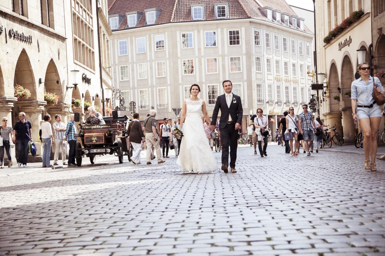 Hochzeit von Laura und Jan in Münster: Brautpaar geht Hand in Hand in der Stadt spazieren