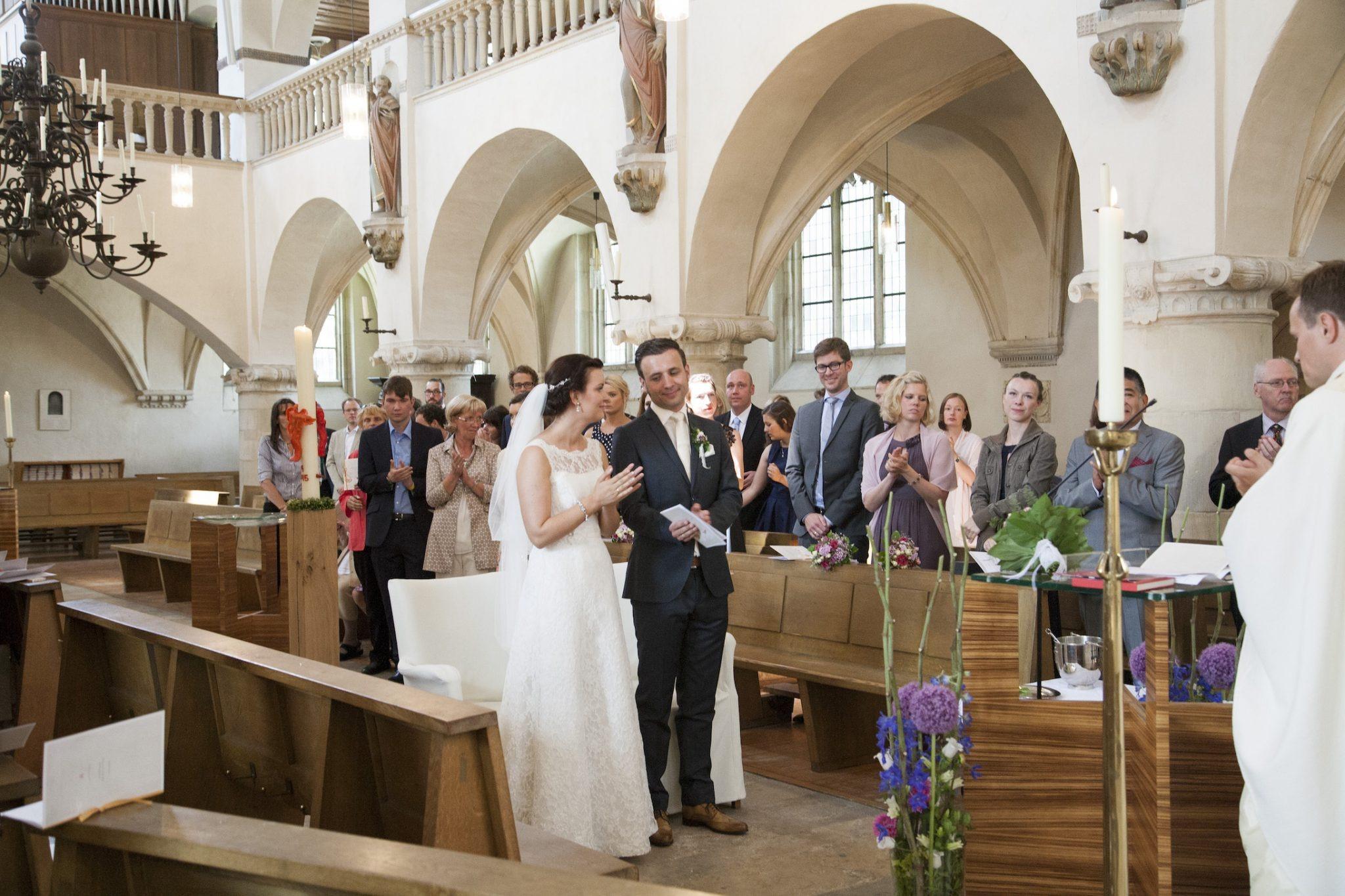 Hochzeit von Laura und Jan in Münster: Brautpaar klatscht in der Kirche