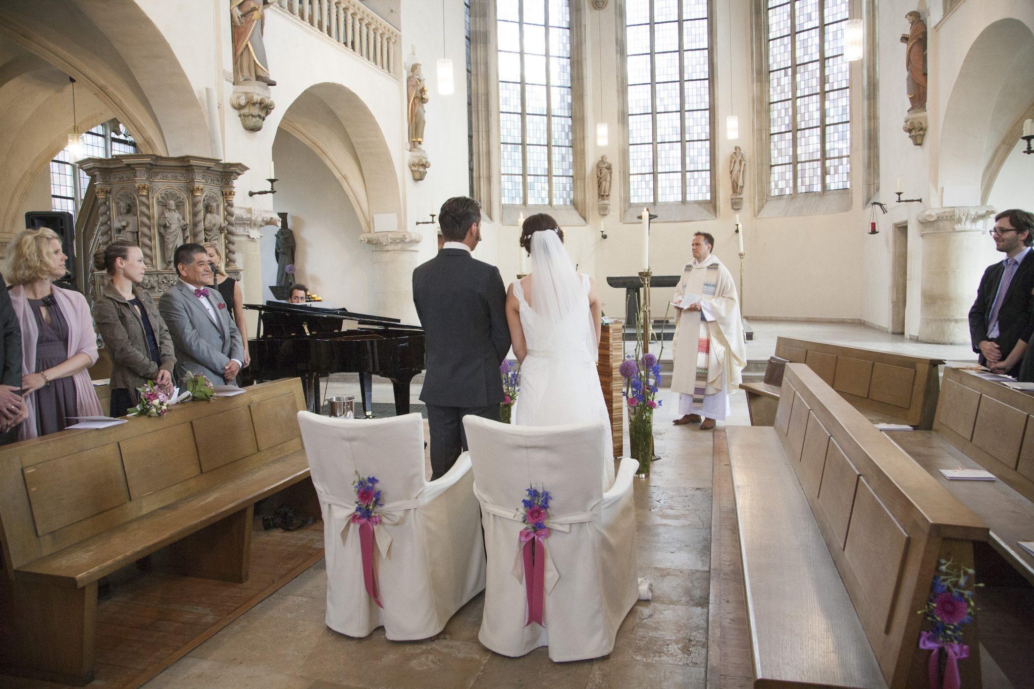 Hochzeit von Laura und Jan in Münster: Brautpaar von hinten in der Kirche