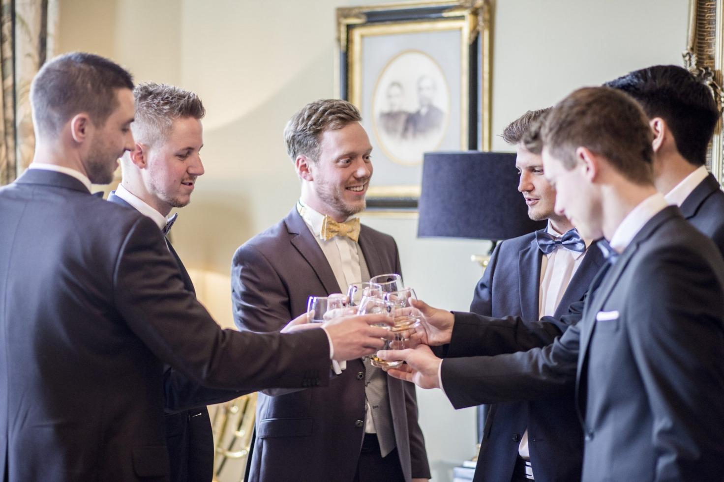 Hochzeit von Jannine und Christian in Münster: Männer die mit einem Getränk anstoßen