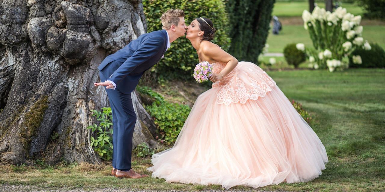 Hochzeit von Tine und Phillip in Münster: Brautpaar küsst sich vor einem Baumstamm