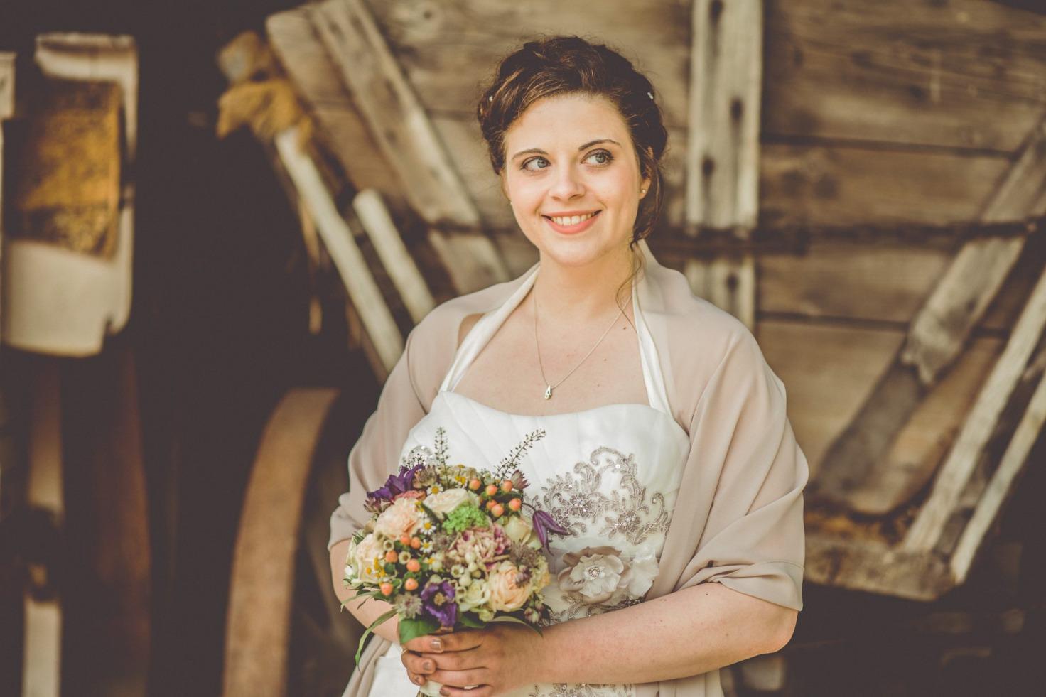 Hochzeit von Bea und Matt in Münster: Braut steht mit dem Brautstrauß vor einem Holzwagen