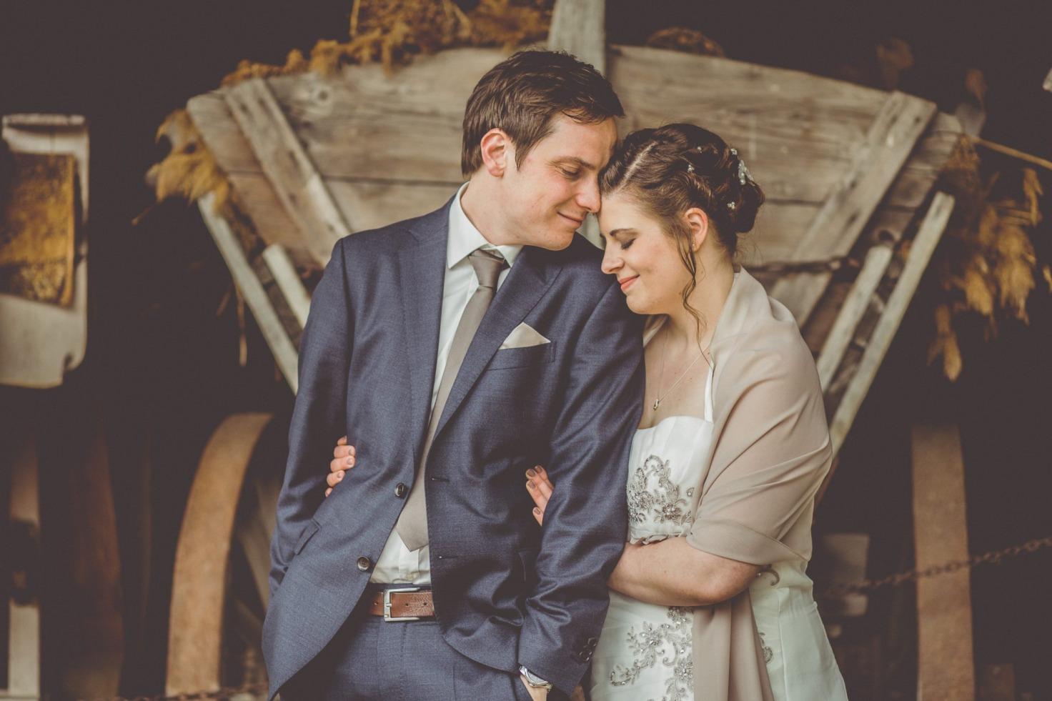 Hochzeit von Bea und Matt in Münster: Brautpaar: Brautpaar steht vor einem Holzwagen
