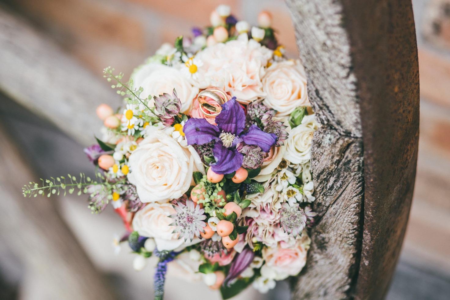 Hochzeit von Bea und Matt in Münster: Brautstrauß liegt auf dem Holzrad
