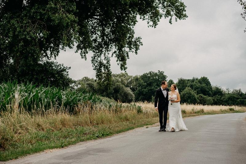 Hochzeit von Anna und Stefan in Münster: Brautpaar geht einen Feldweg entlang