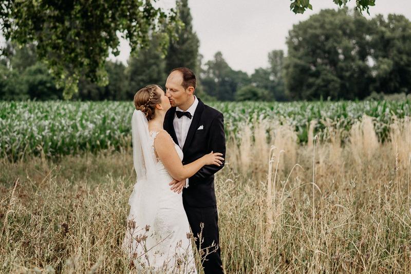 Hochzeit von Anna und Stefan in Münster: Brautpaar küssen sich im Feld
