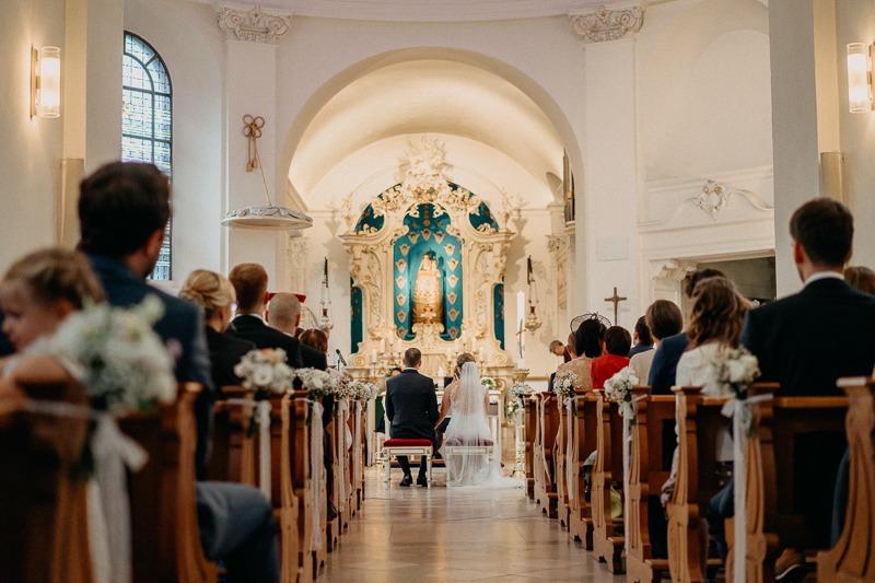 Hochzeit von Anna und Stefan in Münster: Brautpaar von hinten in der Kirche