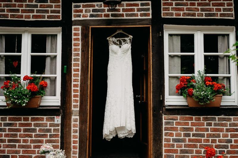Hochzeit von Anna und Stefan in Münster: Brautkleid im Türrahmen