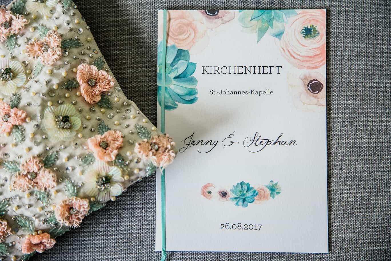 Hochzeit von Jennifer und Stefan in Münster: Kirchenheft mit neben Handtasche
