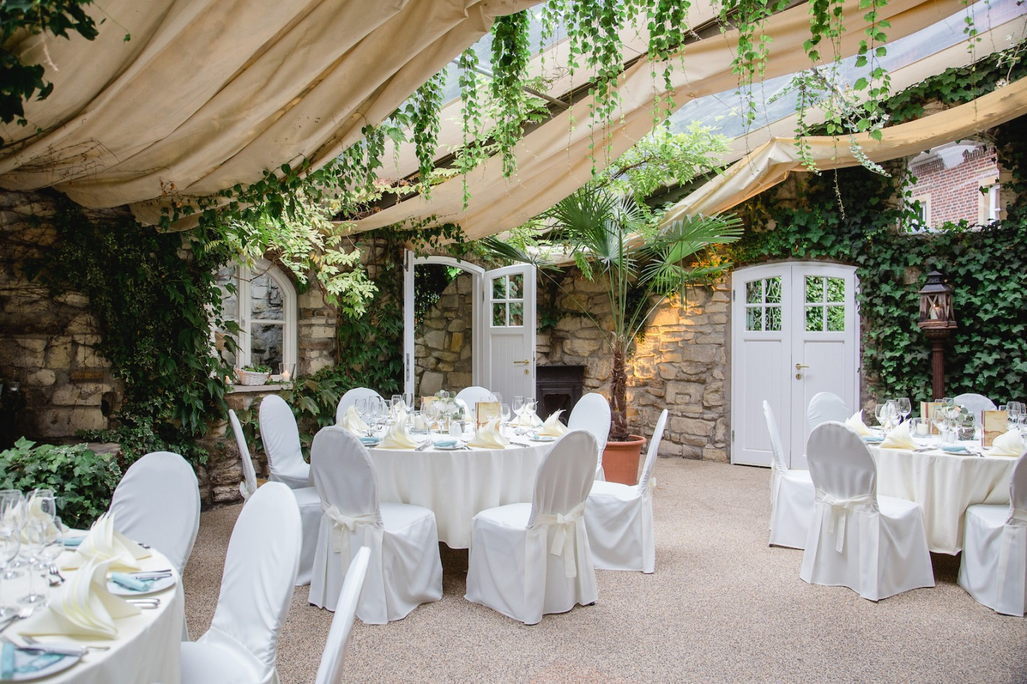 Hochzeit von Jennifer und Stefan in Münster: Geschmückter Saal mit Tischen und Stühlen