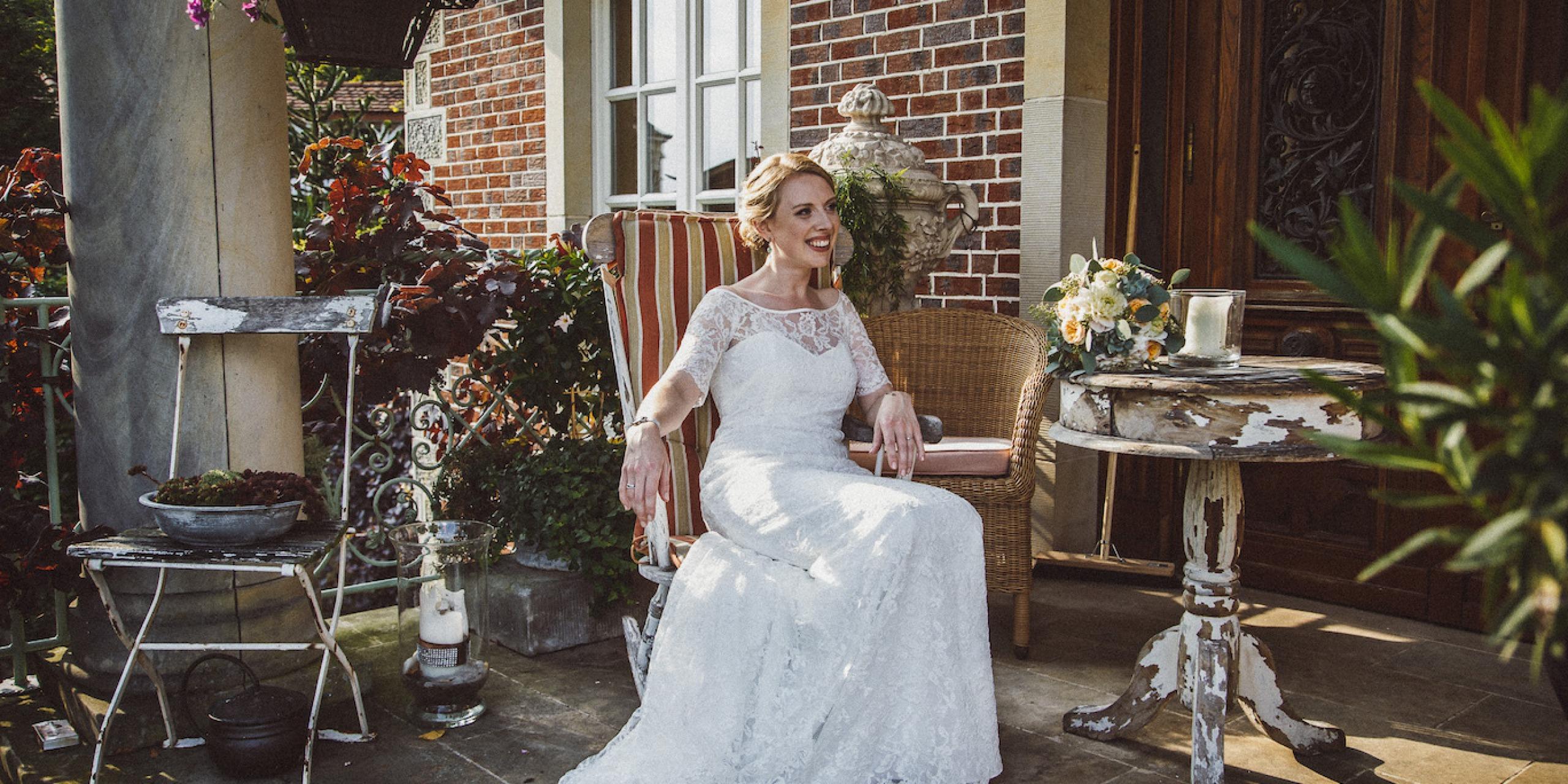 Hochzeit von Jennifer und Stefan in Münster: Braut sitzt auf dem Stuhl und lächelt