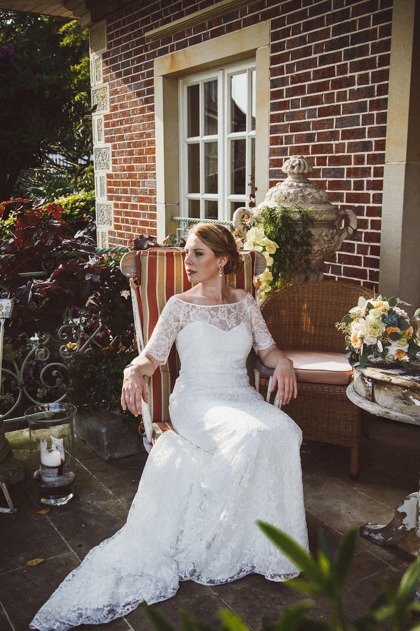 Hochzeit von Jennifer und Stefan in Münster: Braut die auf einem Stuhl sitzt und in die Ferne schaut
