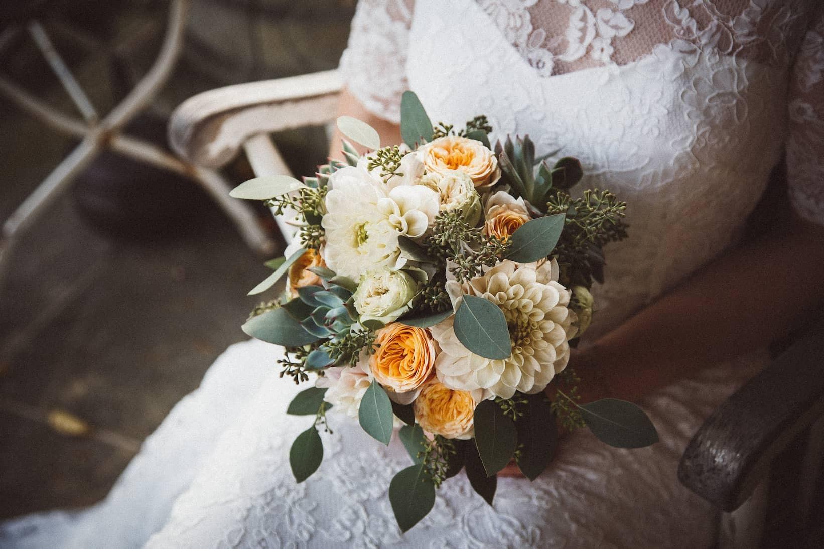 Hochzeit von Jennifer und Stefan in Münster: Braut die ihren Brautstrauß festhält.
