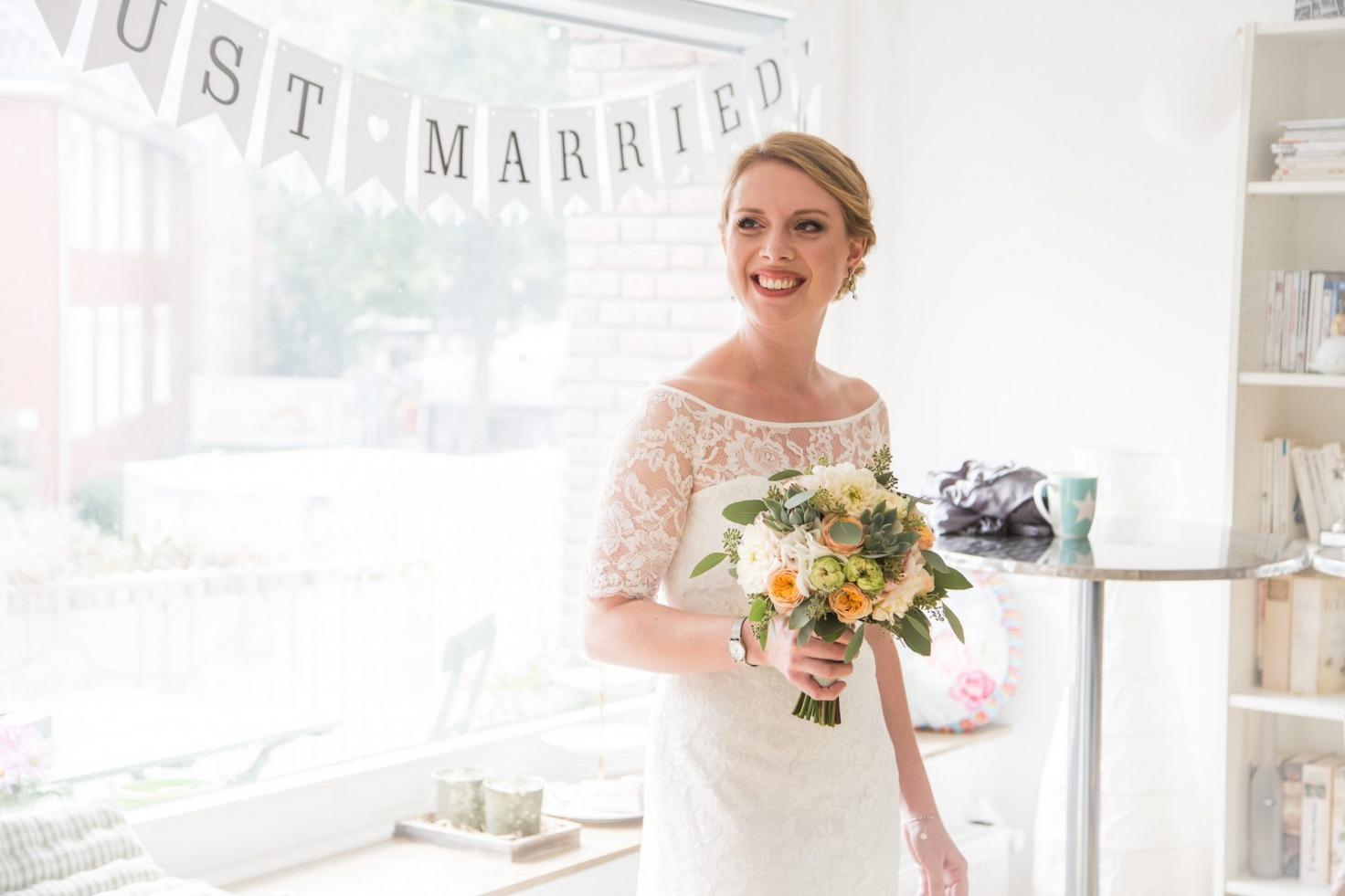 Hochzeit von Jennifer und Stefan in Münster: Braut steht vor dem Fenster und hält ihren Brautstrauß