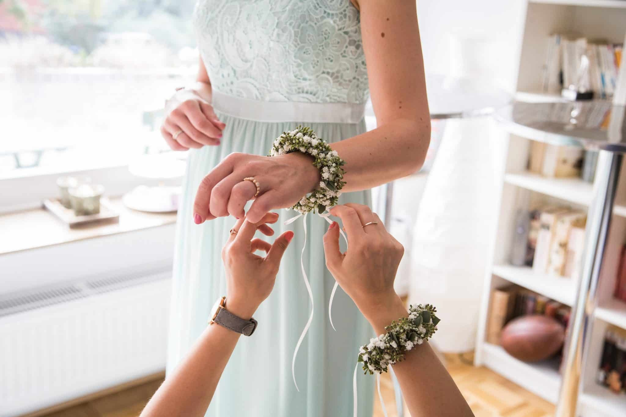 Hochzeit von Jennifer und Stefan in Münster: Blumenkranz wird um das Handgelenk gebunden