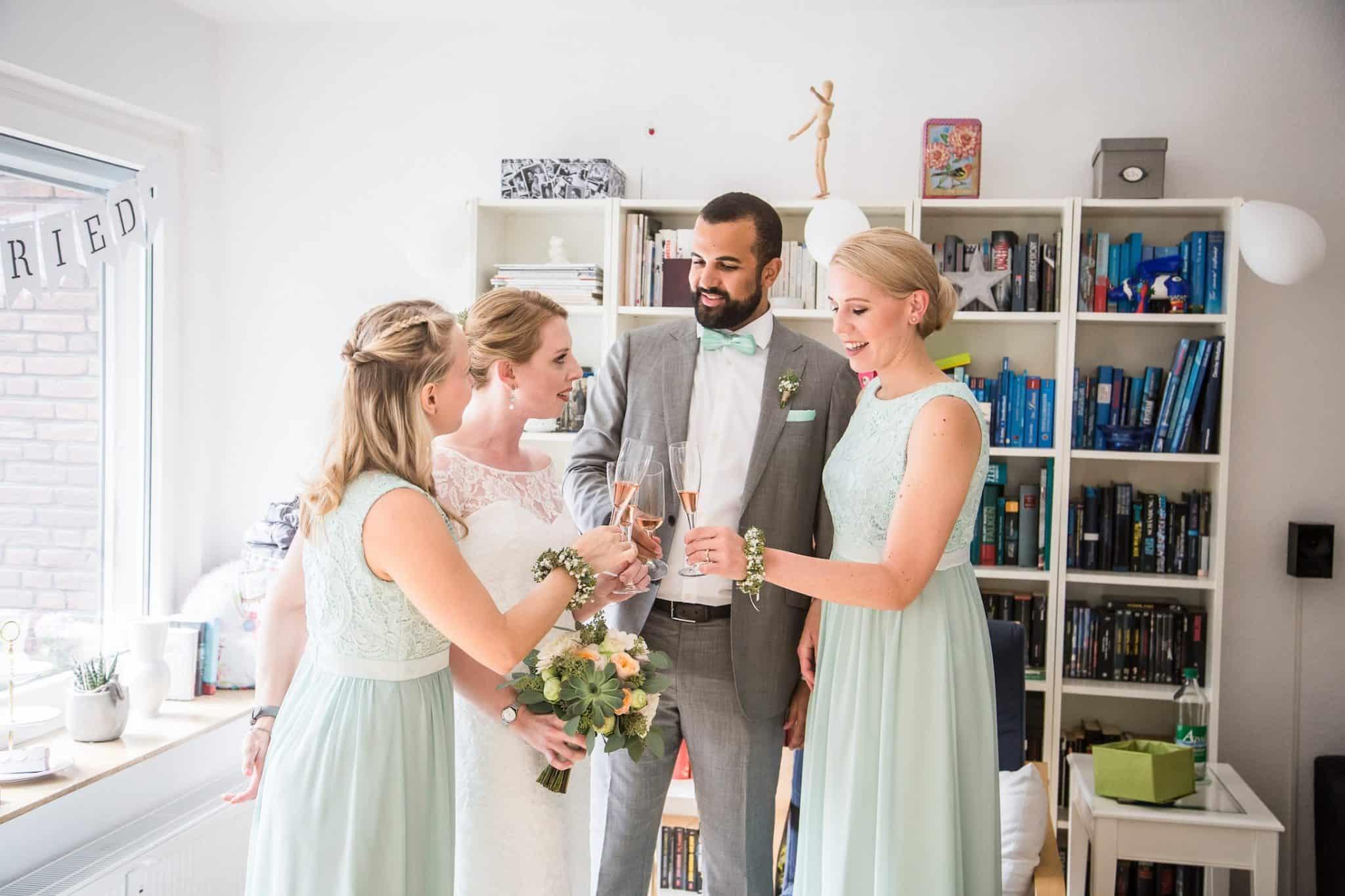 Hochzeit von Jennifer und Stefan in Münster: Braut mit ihren Freunden beim Anstoßen des Sektes