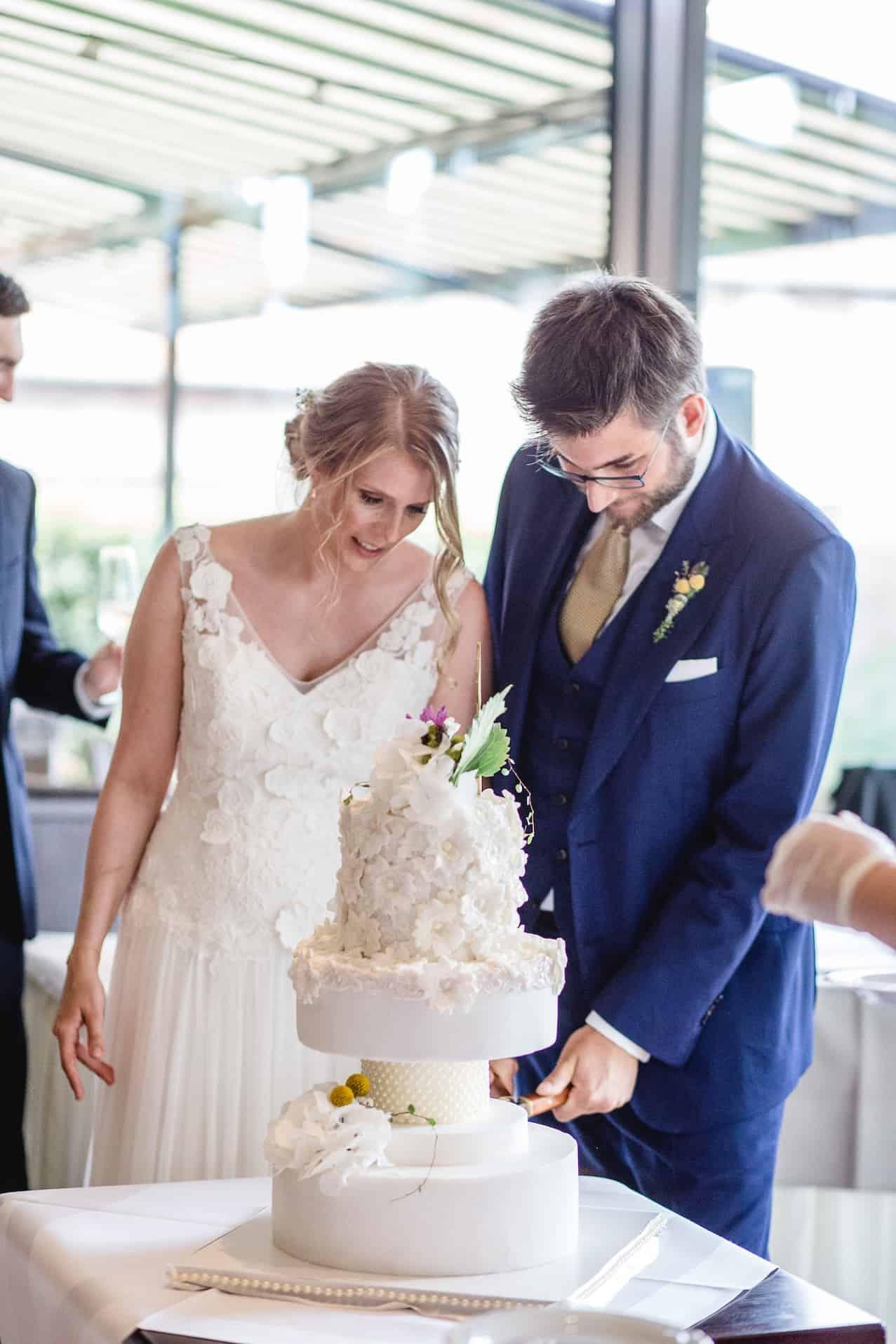 Hochzeit von Laura und Marco in Münster: Brautpaar schneidet gemeinsam die Hochzeitstorte an