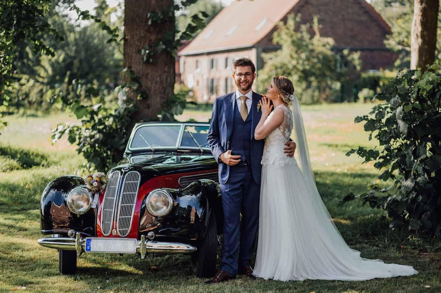 Hochzeit von Laura und Marco in Münster: Brautpaar steht vor einem historischen Auto