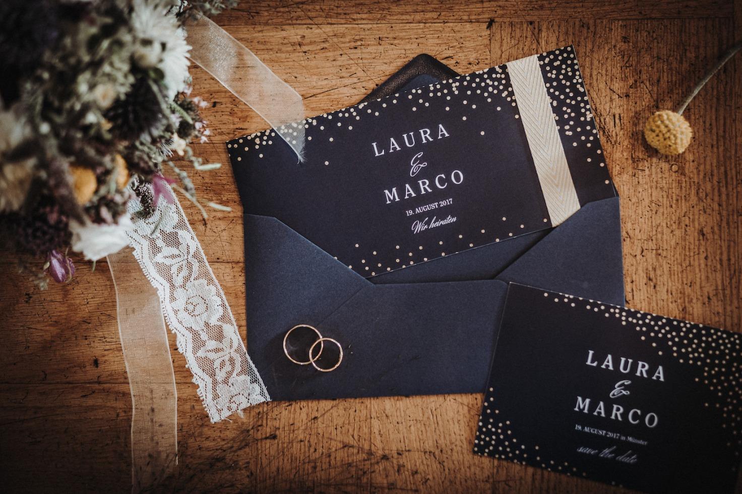 Hochzeit von Laura und Marco in Münster: Hochzeitsringe, die auf der Hochzeitseinladung liegen