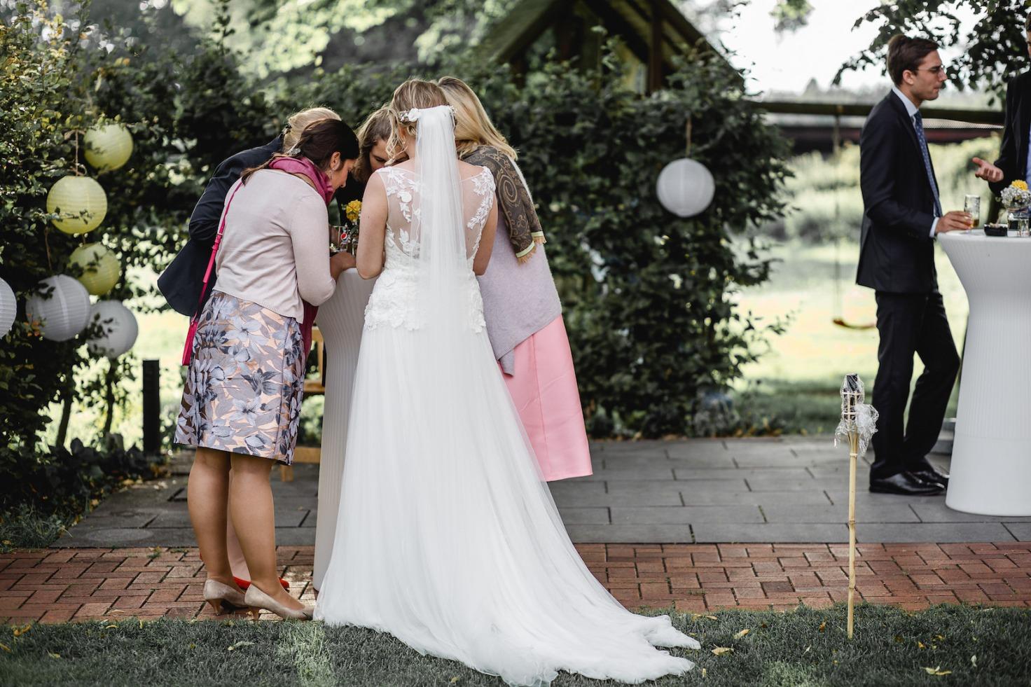 Hochzeit von Laura und Marco in Münster: Braut von hinten mit ihren Gästen
