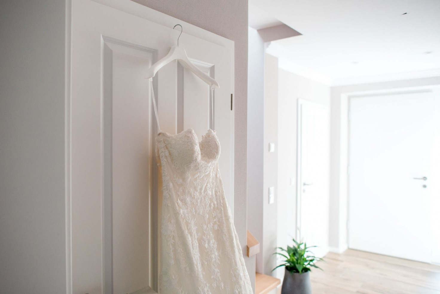 Hochzeit von Sabrina und Michael in Münster: Brautkleid an Tür aufgehangen