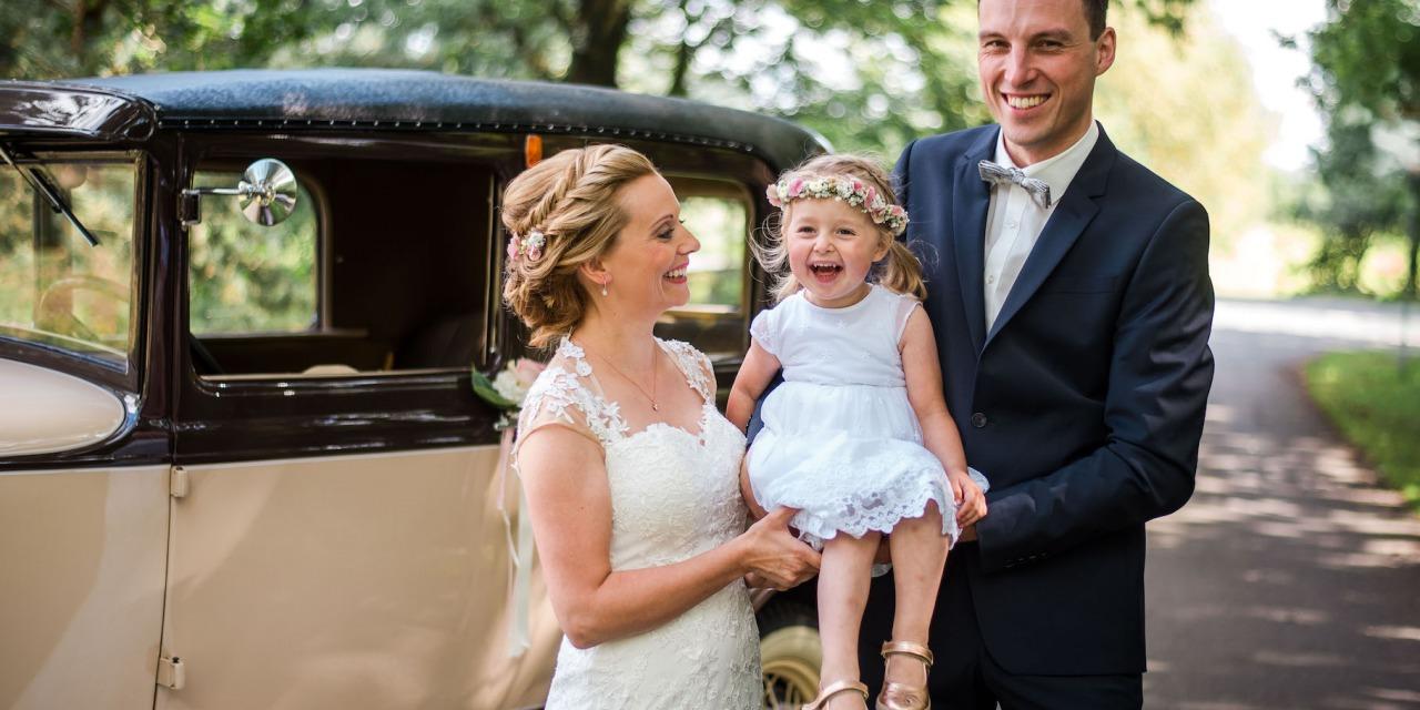 Hochzeit von Sabrina und Michael in Münster: Hochzeitspaar tragen ein Mädchen